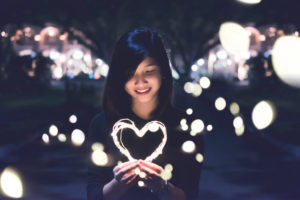 An asian woman holding a heart of light